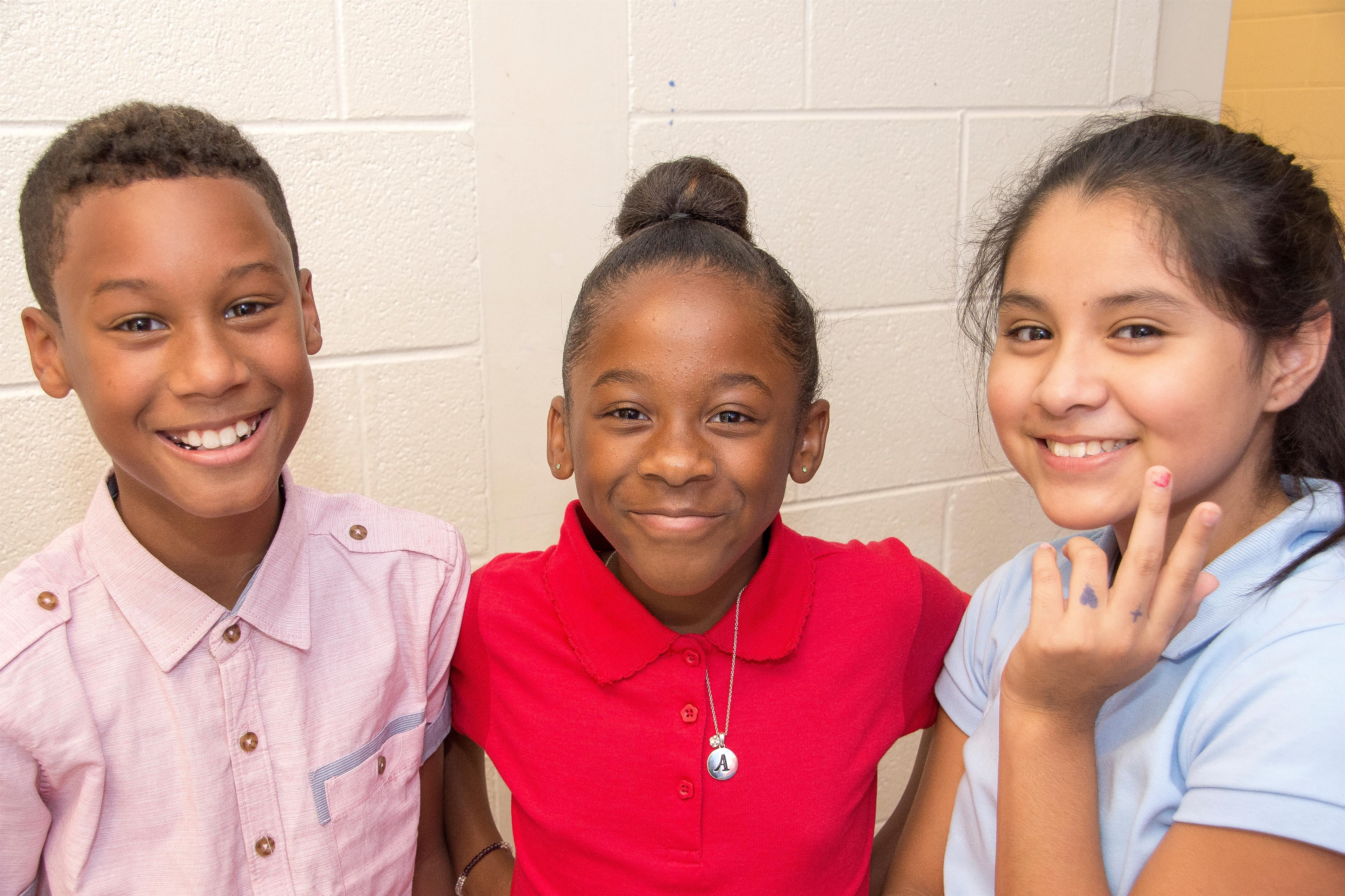 three students smiling